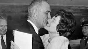 Vice President Lyndon Johnson gets a welcoming kiss from Lady Bird Johnson at Andrews Air Force base on Aug. 21, 1961.