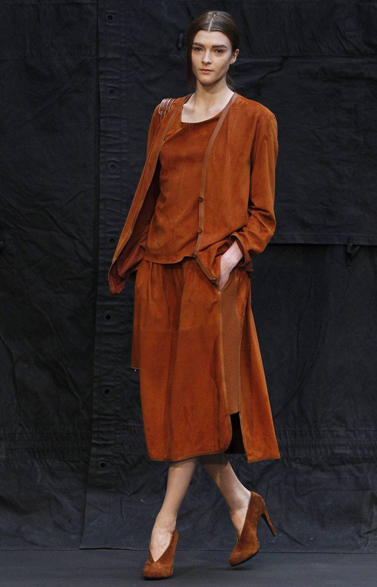 In addition to suede sweatpants with rolled ribbed cuffs, Lemaire (who previously designed for Lacoste) expressed his sportier side with stretch panels, seen running up the side of this marigold suede dress.