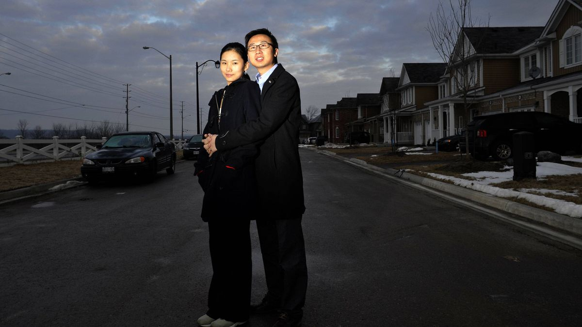 Lily Miao and her husband Dong Wang outside their newly completed home in the west end of Milton.