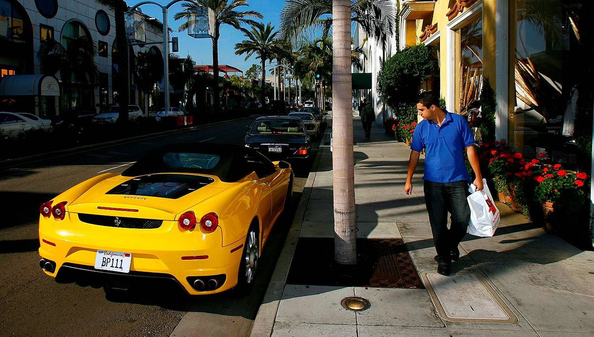 A man glances at a Ferrari sports car while visiting businesses that cater to high-end luxury item consumers along Rodeo Drive on December 14, 2007 in Beverly Hills, California. In the midst of the biggest selling season of the year, retailers for America's richest consumers are losing their least-affluent customers, those who buy luxury items only when they have the cash to spend, while the richest continue buying designer merchandise at a healthy clip. Masking the extent of the decline could be the weakened US dollar which has increased the flow of foreign tourists shopping in major US cities. (Photo by David McNew/Getty Images)