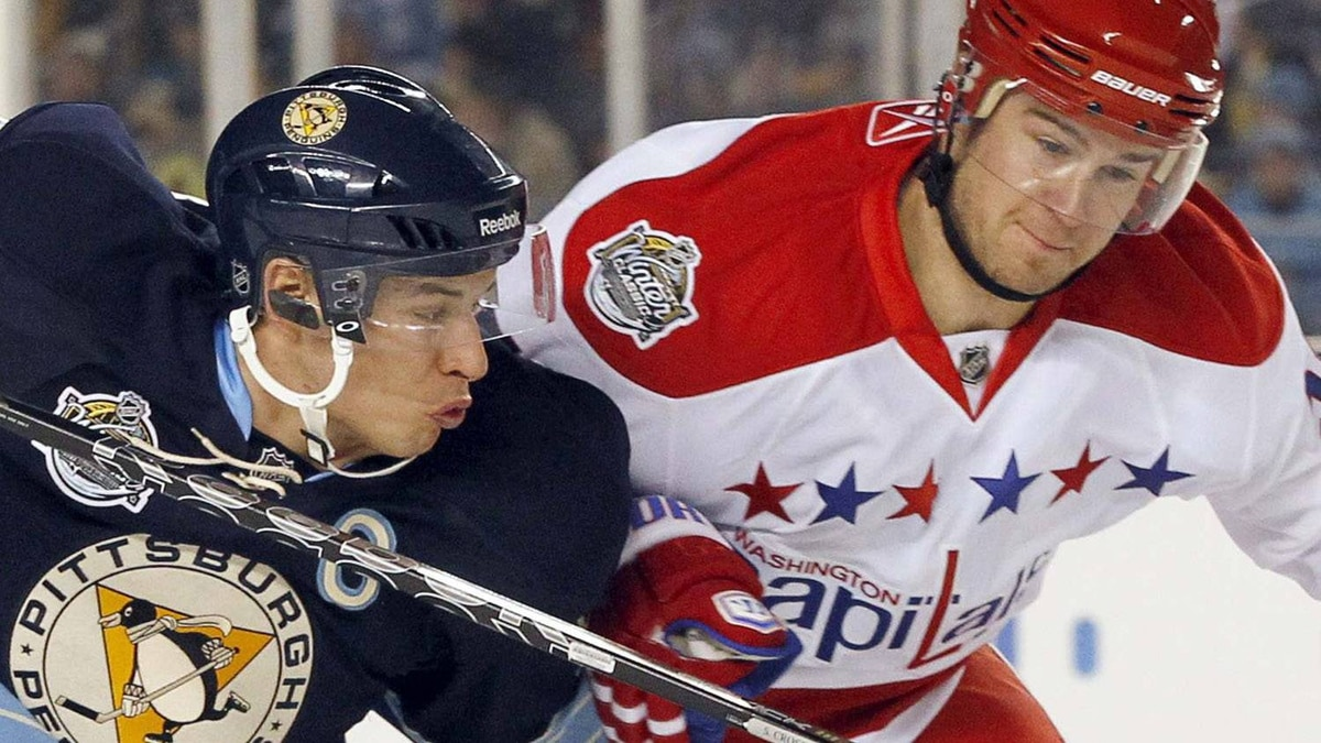 Pittsburgh Penguins center Sidney Crosby (L) and Mike Green (R) of the Washington Capitals fight for the puck during the first period of the NHL's Winter Classic hockey game at Heinz Field in Pittsburgh, Pennsylvania January 1, 2011. REUTERS/Jason Cohn