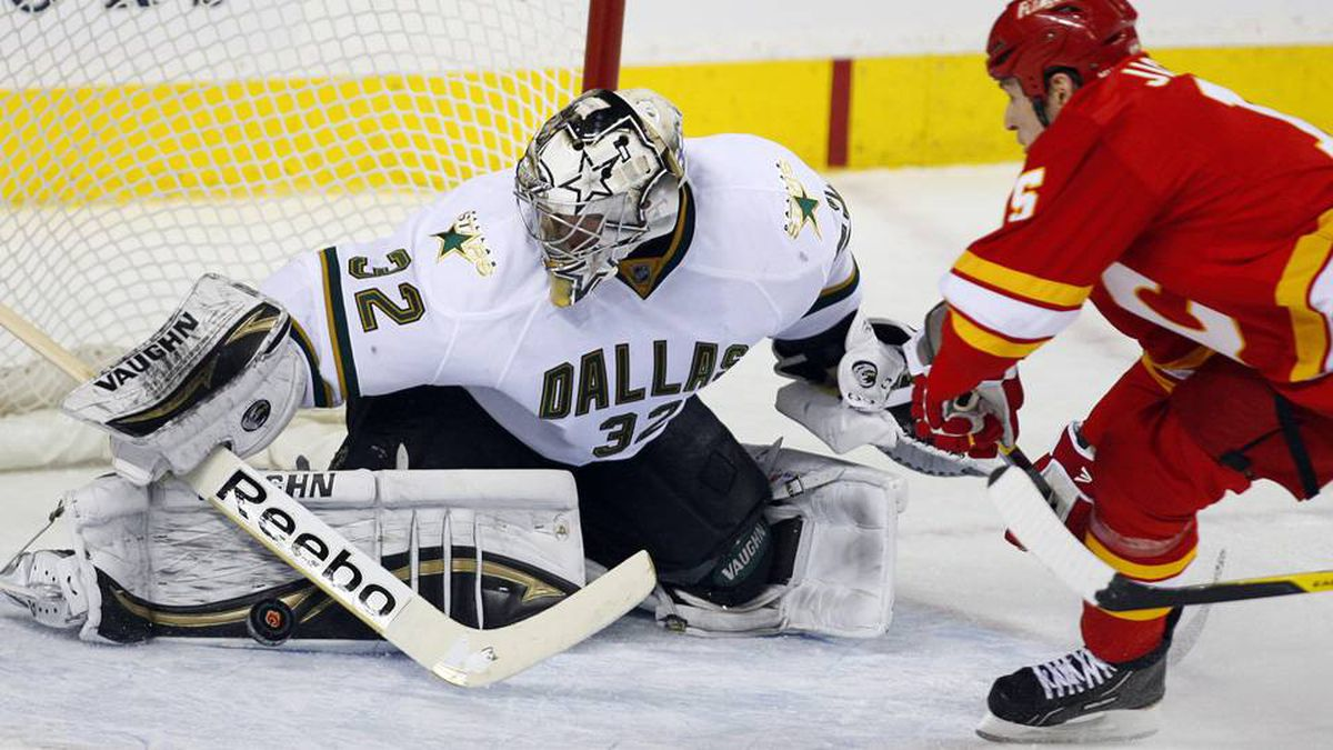 Dallas Stars goalie Kari Lehtonen, left, from Finland, blocks a shot from Calgary Flames' Tim Jackman during second period NHL hockey action in Calgary, Alta., Sunday.