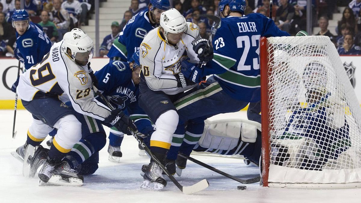 Joel Ward #29 and Martin Erat #10 of the Nashville Predators dig for the loose puck while Alexander Edler #23, Christian Ehrhoff #5 of the Vancouver Canucks helps dfend on the play after goalie Roberto Luongo #1 of the Vancouver Canucks was knocked into his net during the first period. (Photo by Rich Lam/Getty Images)