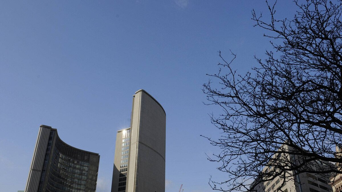 The two curved towers at Toronto city hall are visible above the elevated walkway at Nathan Phillip Square on February 28 2012.