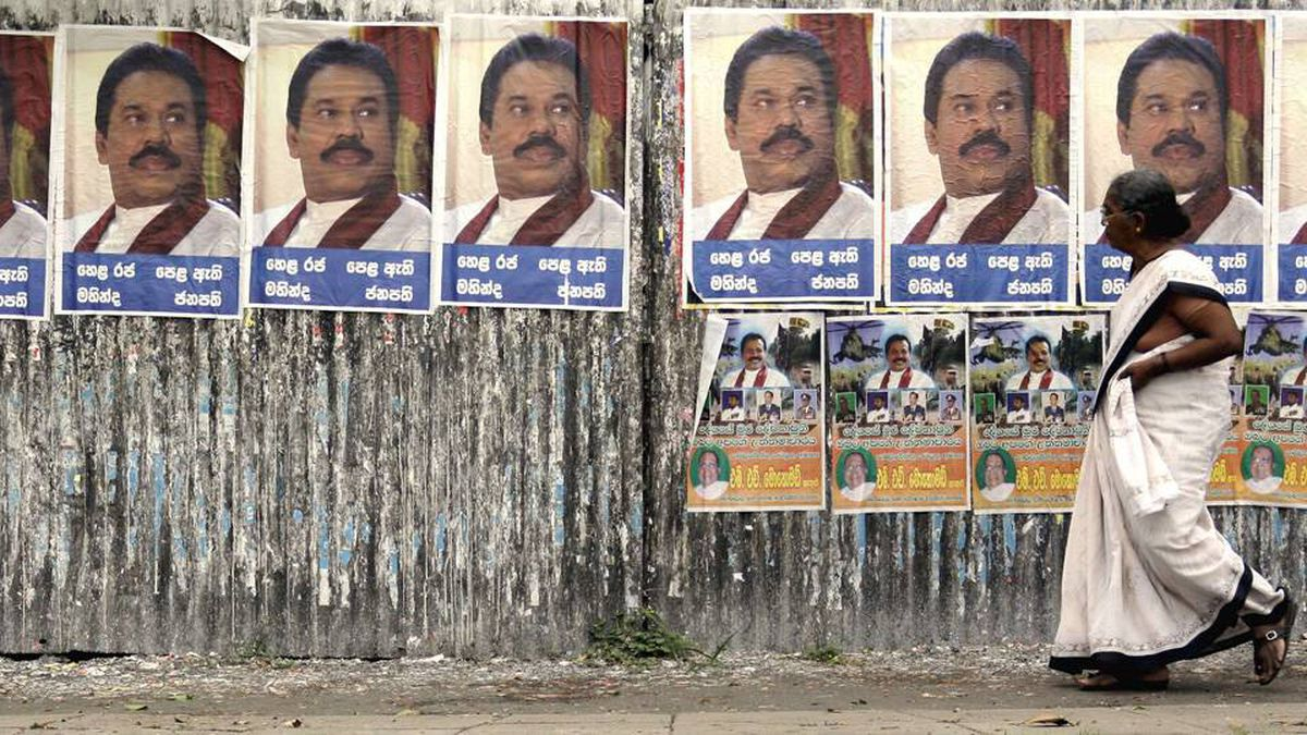 A woman walks past posters bearing the portrait of Sri Lankan President Mahinda Rajapaksa along a main street in central Colombo recently.