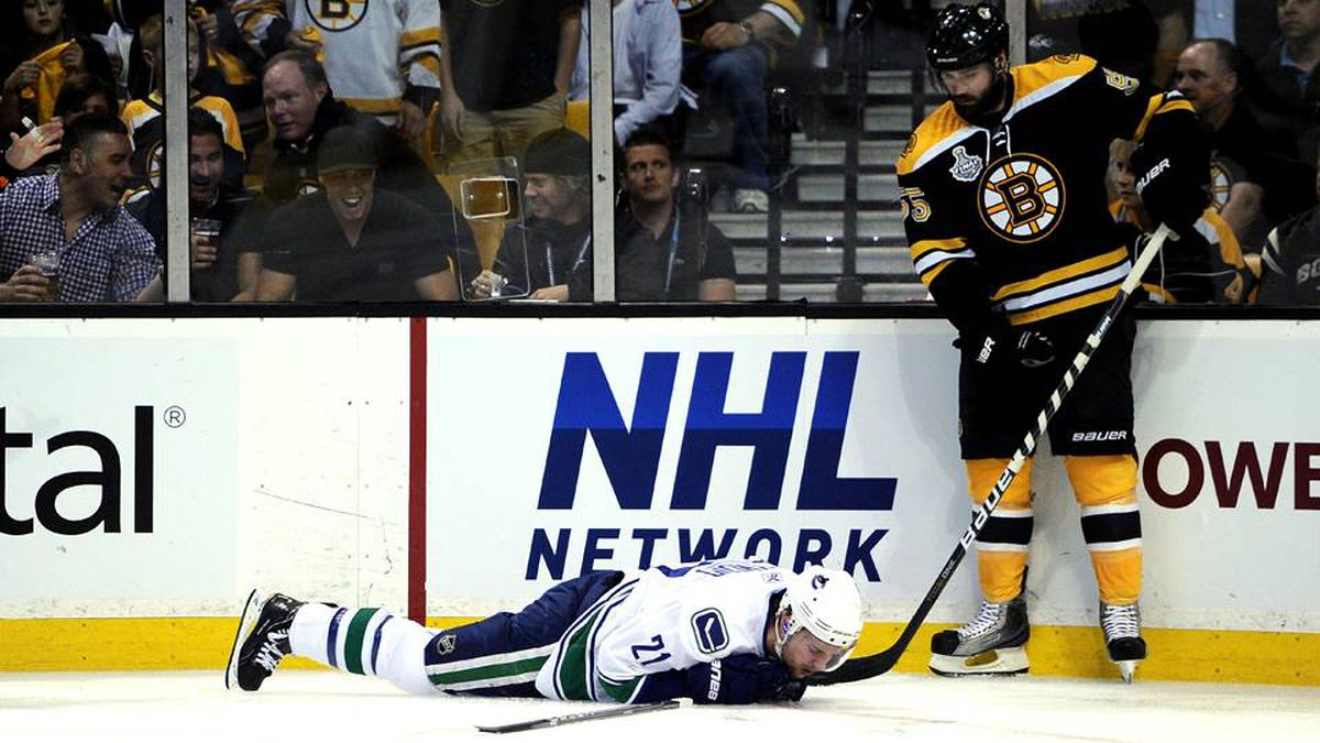 Mason Raymond of the Vancouver Canucks lays on the ice after being checked by Johnny Boychuk of the Boston Bruins.