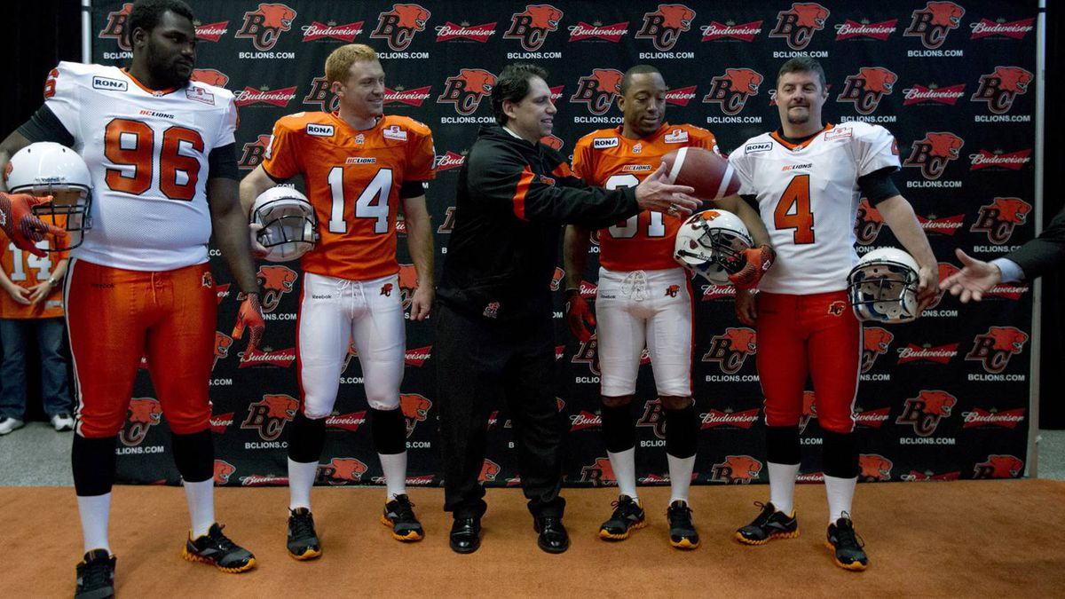 B.C. Lions Khalif Mitchell (96), Travis Lulay (14) head coach Mike Benevides, Geroy Simon (81) and Paul Mitchell (4) show off the teams new jerseys at a news conference in Vancouver, May 2, 2012.