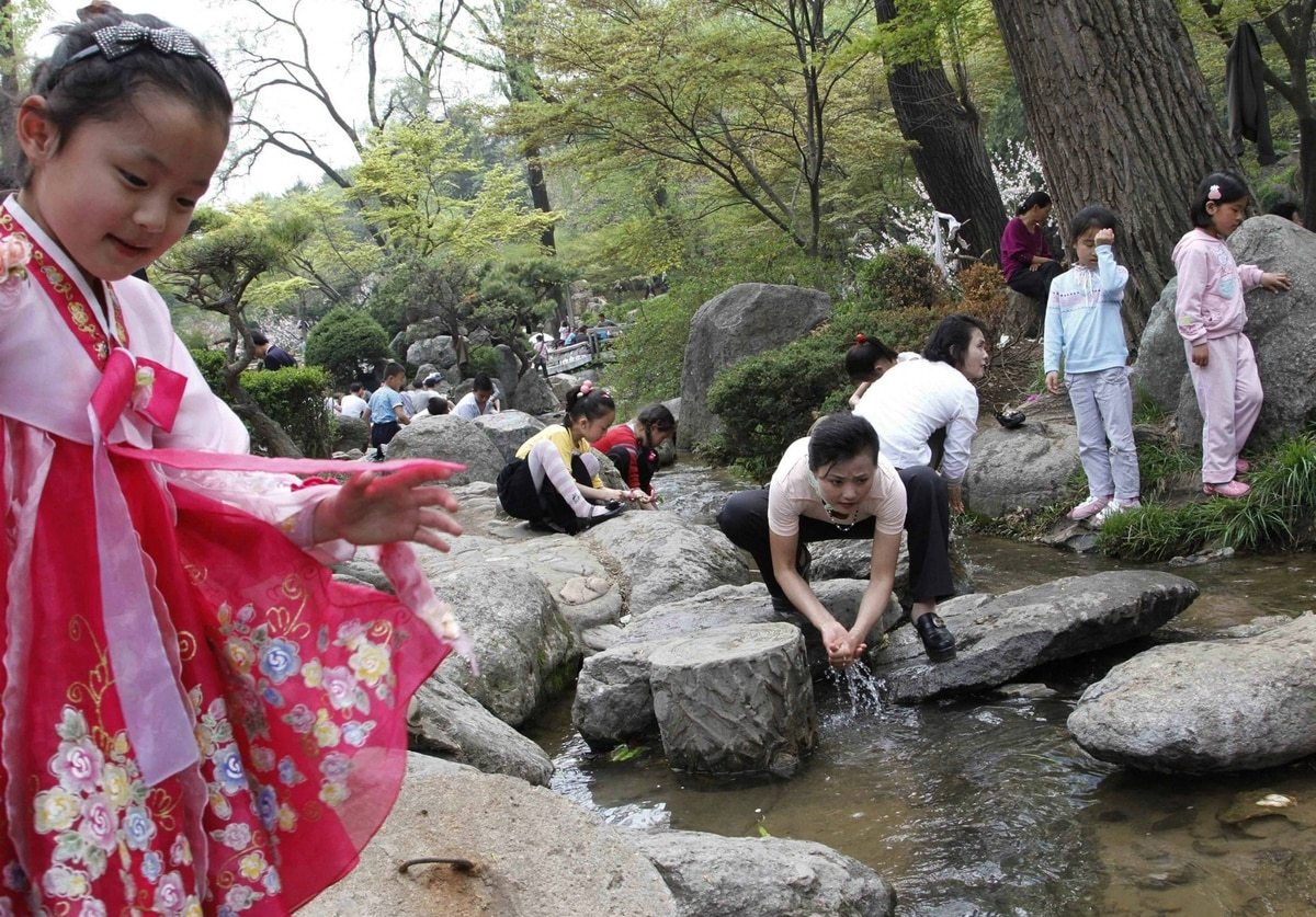 North Koreans dip their hands in a stream in Pyongyang, North Korea, on May Day. North Korean families flocked to parks, playgrounds and plazas to enjoy the May Day holiday with picnics, cultural events and games.
