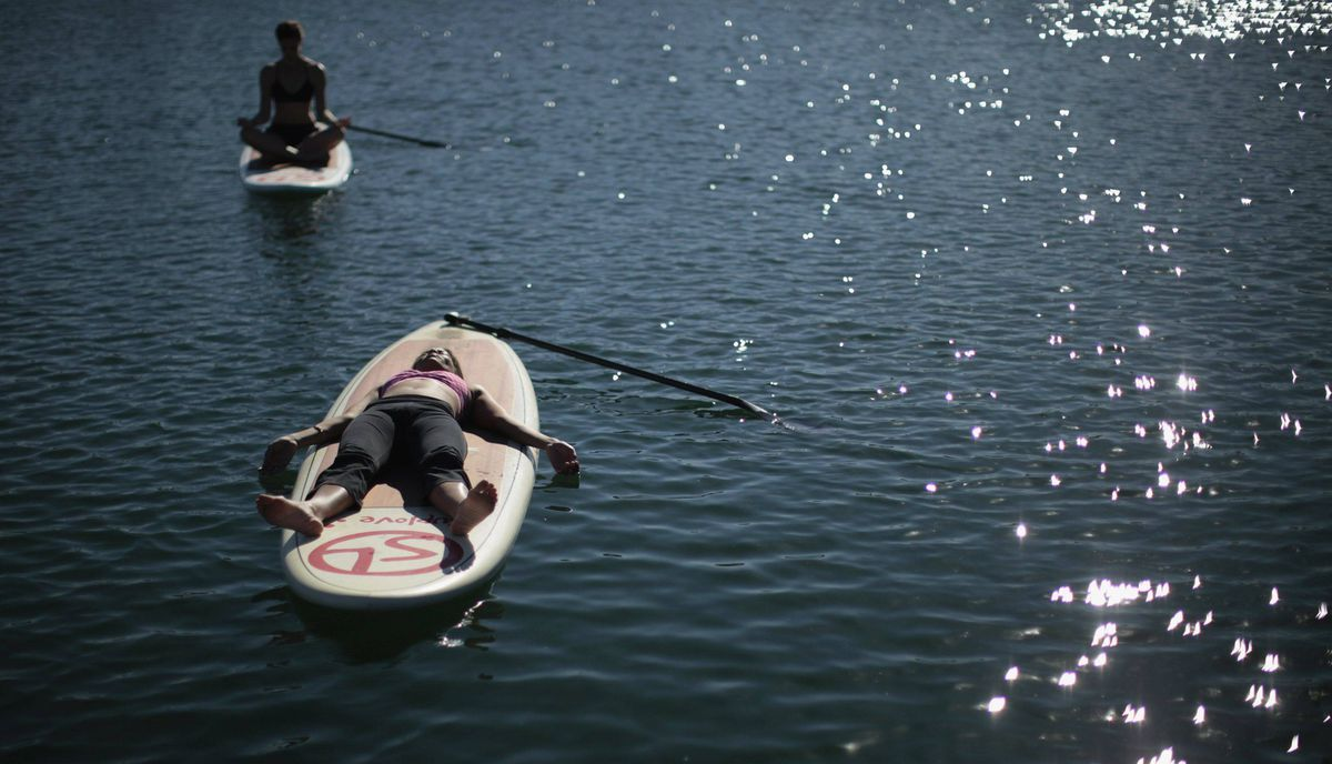 Chelsea McElroy, 40, (R) and Claire Robbie, 31, rest during a Yogaqua class, which combines yoga and paddleboarding, in Marina Del Rey, Los Angeles January 28, 2012.