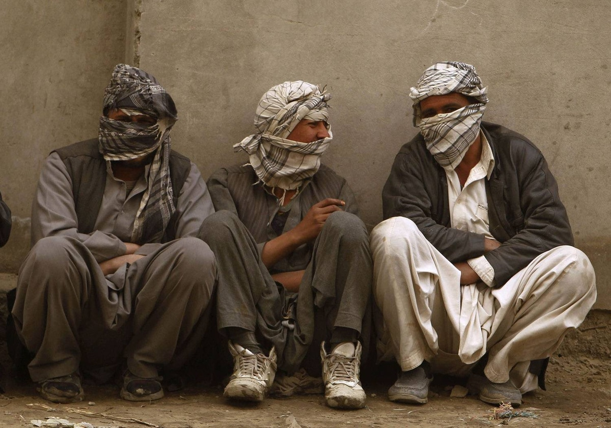 Afghan men cover themselves during a wind storm in Kabul March 19, 2012.