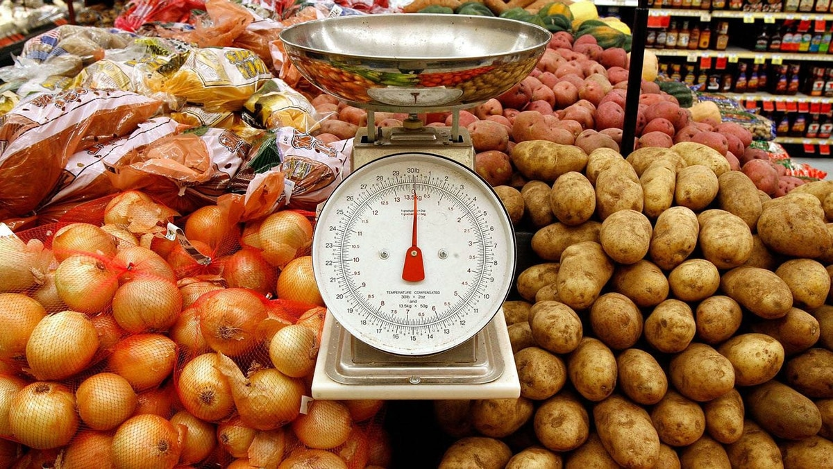 Onions and potatoes and a weigh scale in the produce section of a grocery store.