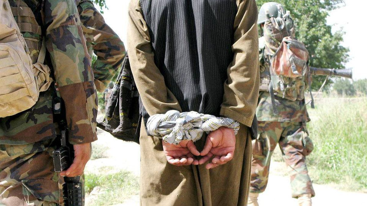 A man Afghan authorities suspect of insurgency-related activities is interrogated during a joint Canadian-Afghan army patrol in the Panjwaii District of Kandahar province on July 2, 2009.