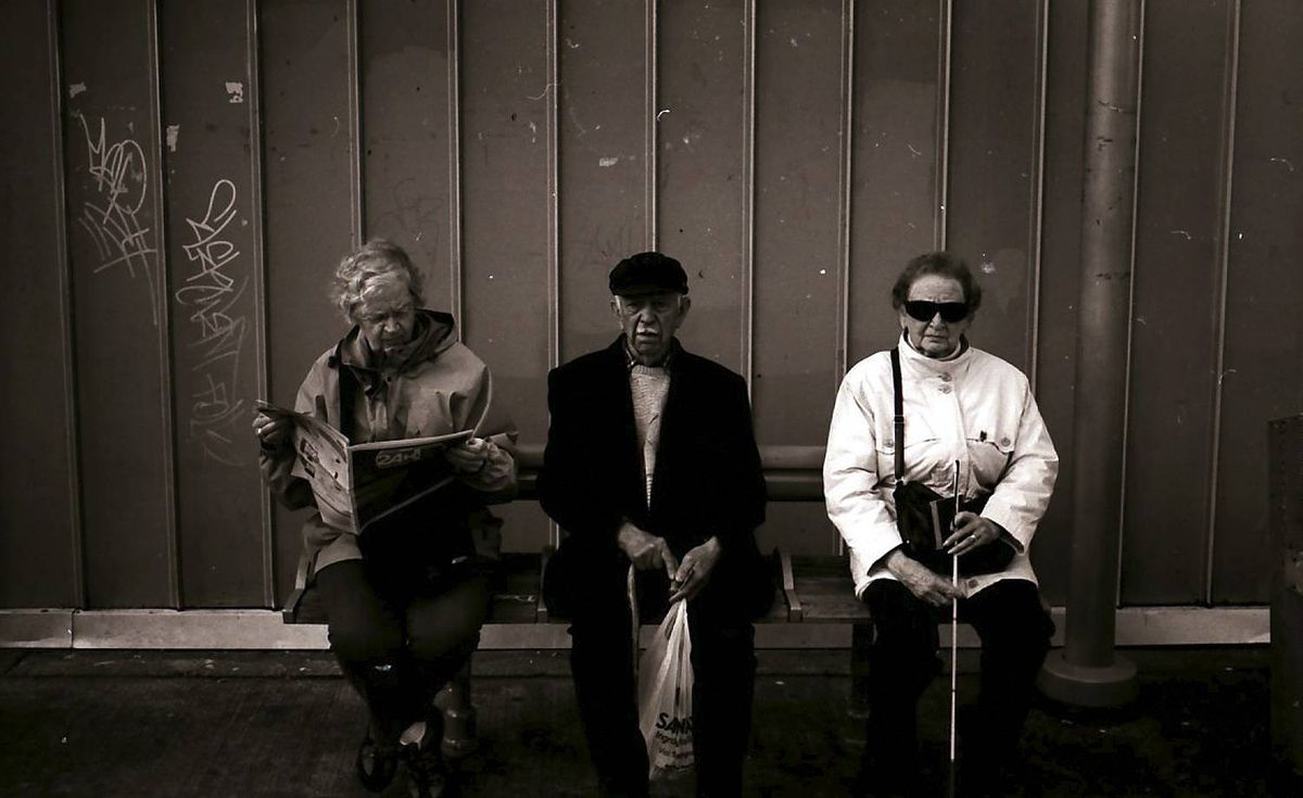 Robert Fougere uploaded this image to our Flickr pool of three people waiting for a bus.