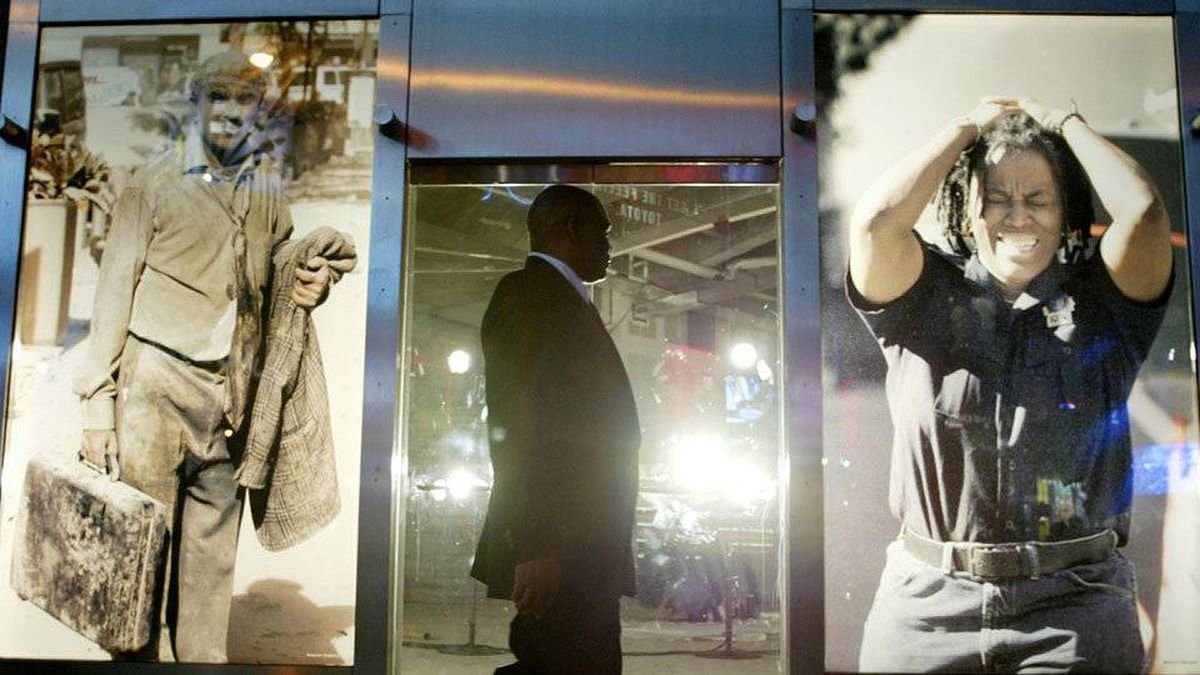 A man walks past a window display of photos in Times Square of the collapse of the World Trade Center in New York, September 10, 2002.