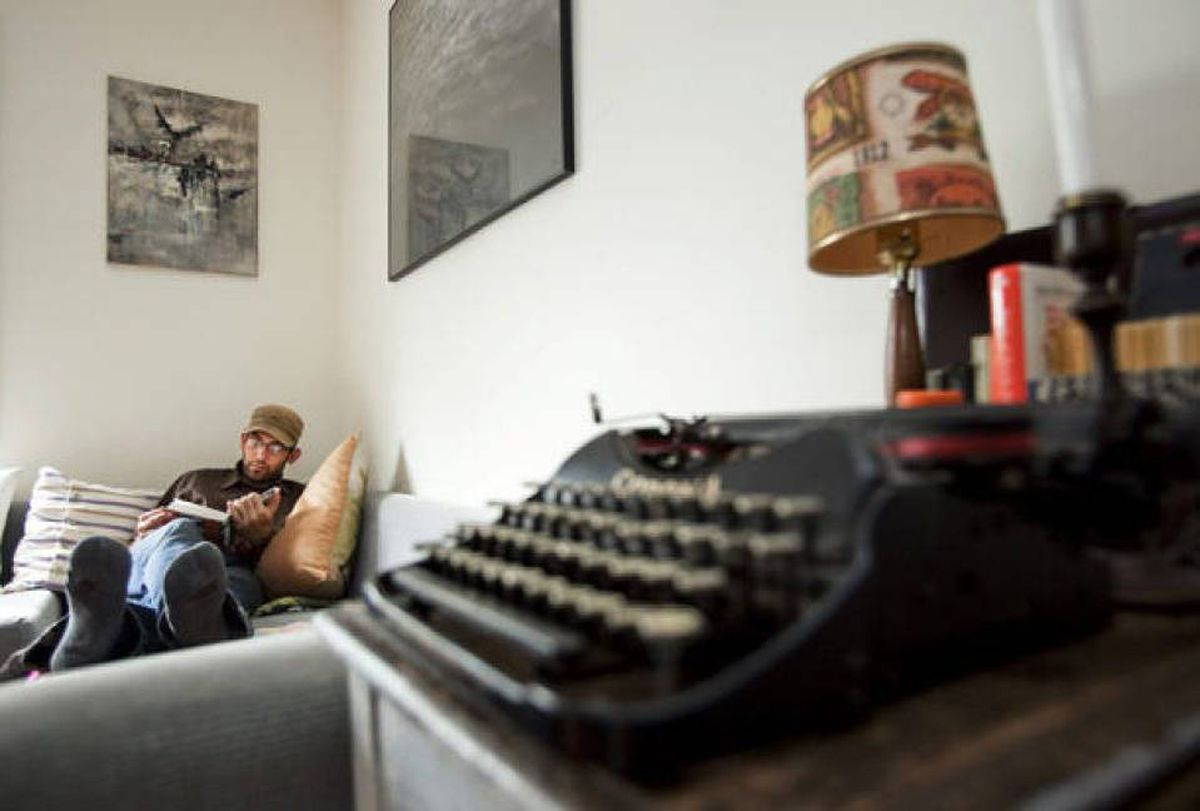 Pasha Malla reads in his living room in Toronto.