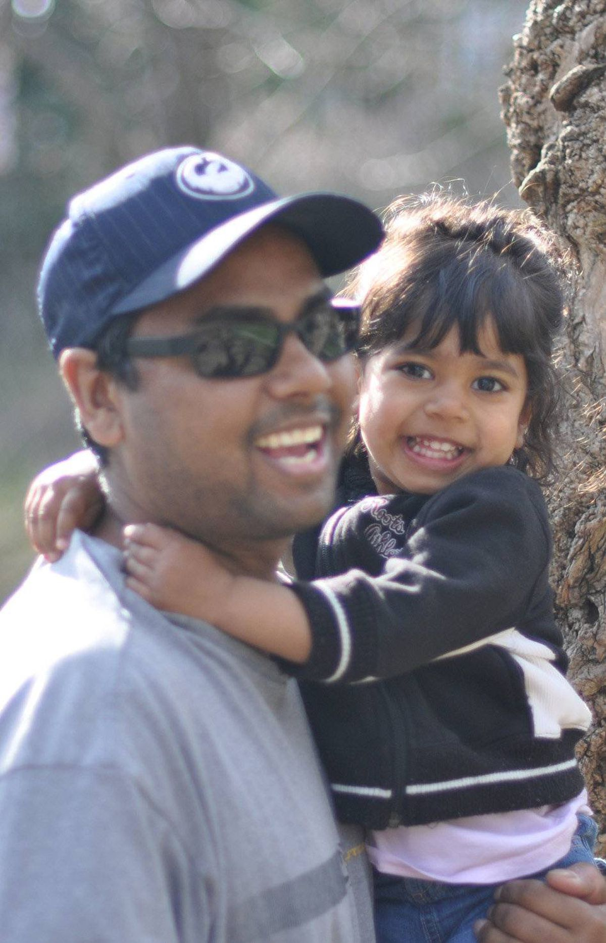 "Here's Eshana and her Dad last month (May 2011) hanging out in the Beaches. She loves the sights and sounds of being outside. We hope she always enjoys nature and snuggling with her ""Dada""."