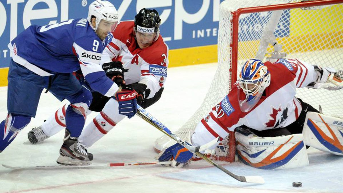 Damien Fleury of France, left, tries to score against Canada's Dion Phaneuf and goalie Devan Dubryk during their Ice Hockey World Championships in Helsinki