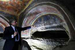 Catacomb archeological superintendent Fabrizio Bisconti points to frescoes discovered with the earliest known icons of the Apostles Peter and Paul in a catacomb located under a modern office building in a residential neighborhood of Rome, Tuesday, June, 22, 2010. Restorers said Tuesday they had unearthed the 4th-century images using a new laser technique that allowed them to burn off centuries of white calcium deposits without damaging the dark colors of the original paintings underneath. The paintings adorn what is believed to be the tomb of a Roman noblewoman and represent some of the earliest evidence of devotion to the apostles in early Christianity.