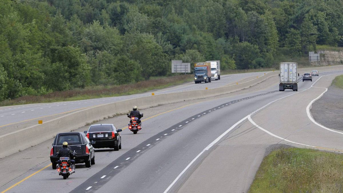 Accompanied by two police motorcycle escorts, the hearse carrying the body of Jack Layton heads east along the 401 near Brockville, Ont. as it makes its way to Ottawa.