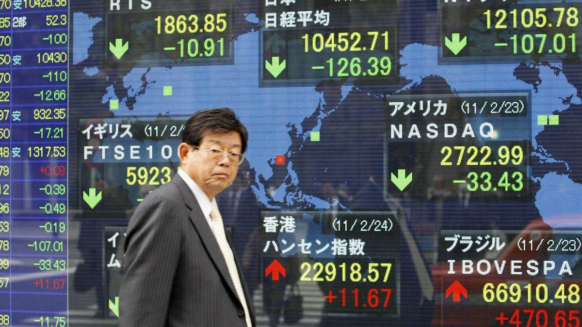 A man walks by an electronic stock indicator in Tokyo as Japan's Nikkei 225 stock average lost 126.39 points, or 1.1 percent to 10,452.71 Thursday, Feb. 24, 2011.