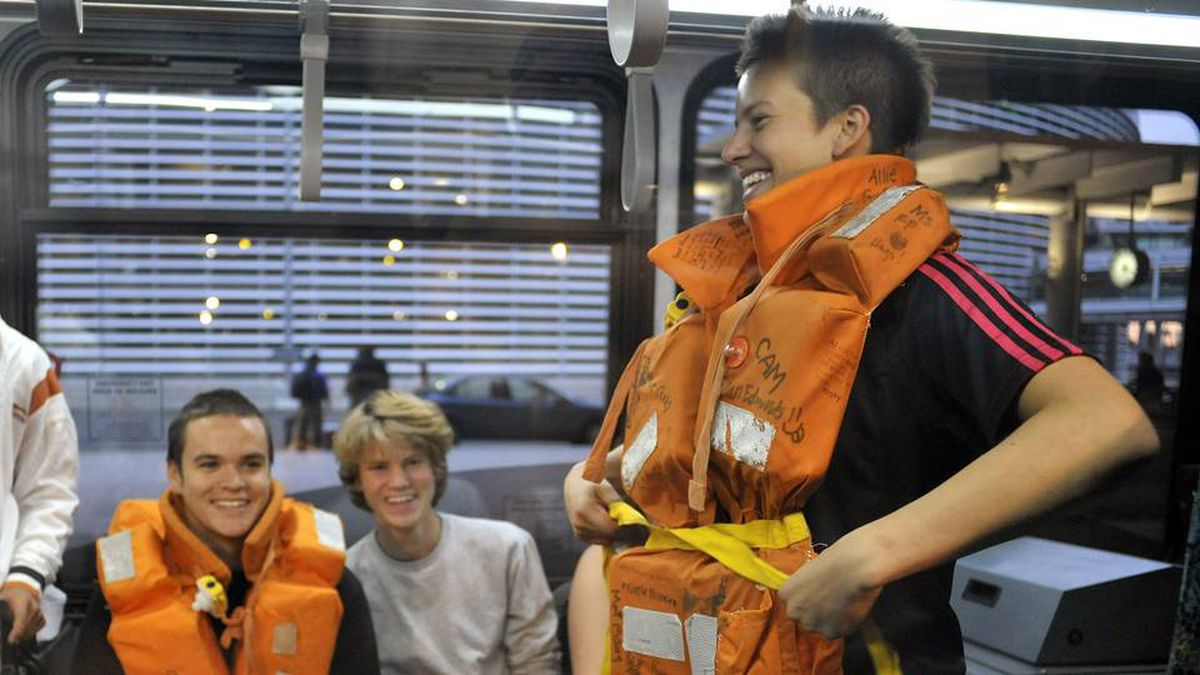 A group of Calgary students who survived the sinking of their floating classroom tallship the Concordia, try on their life vests on board an airport shuttle bus after landing at Pearson airport in Toronto, February 22, 2010.