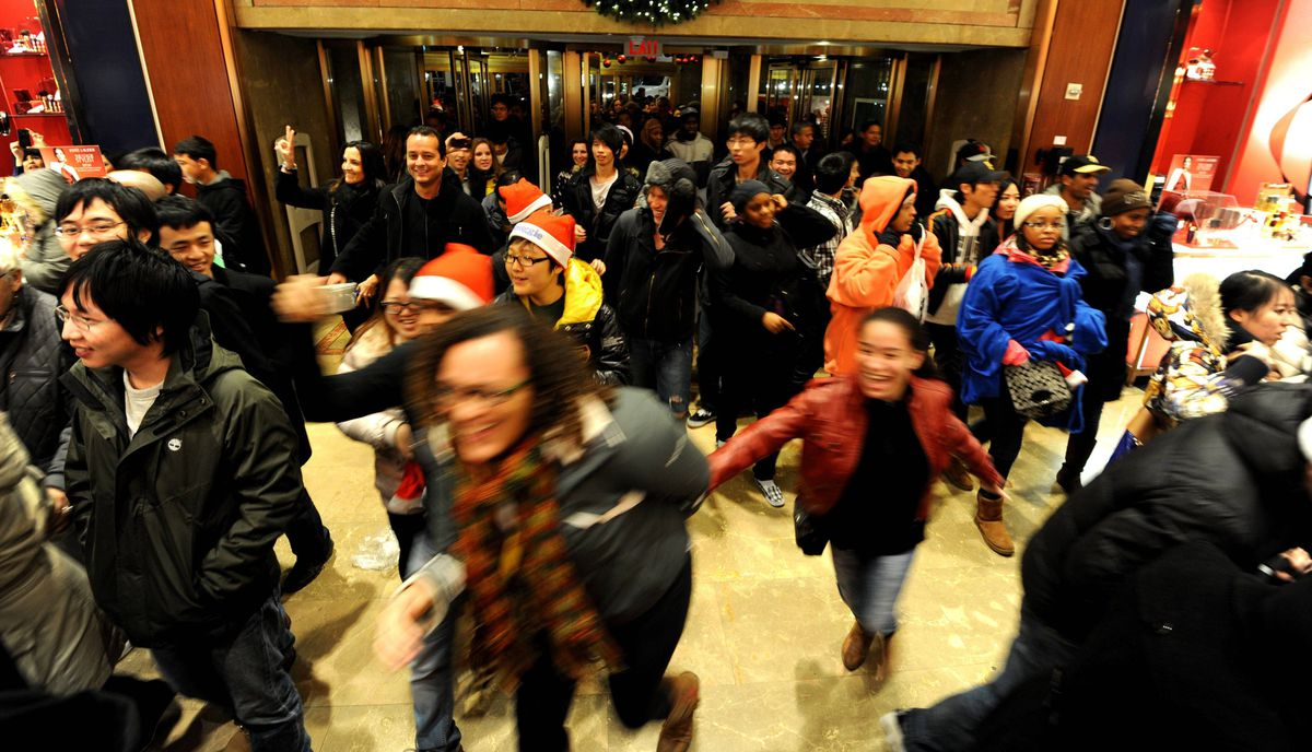 "People rush into the entrance of Macy's department store as they open at midnight on November 25, 2011 in New York to begin the ""Black Friday"" shopping weekend."