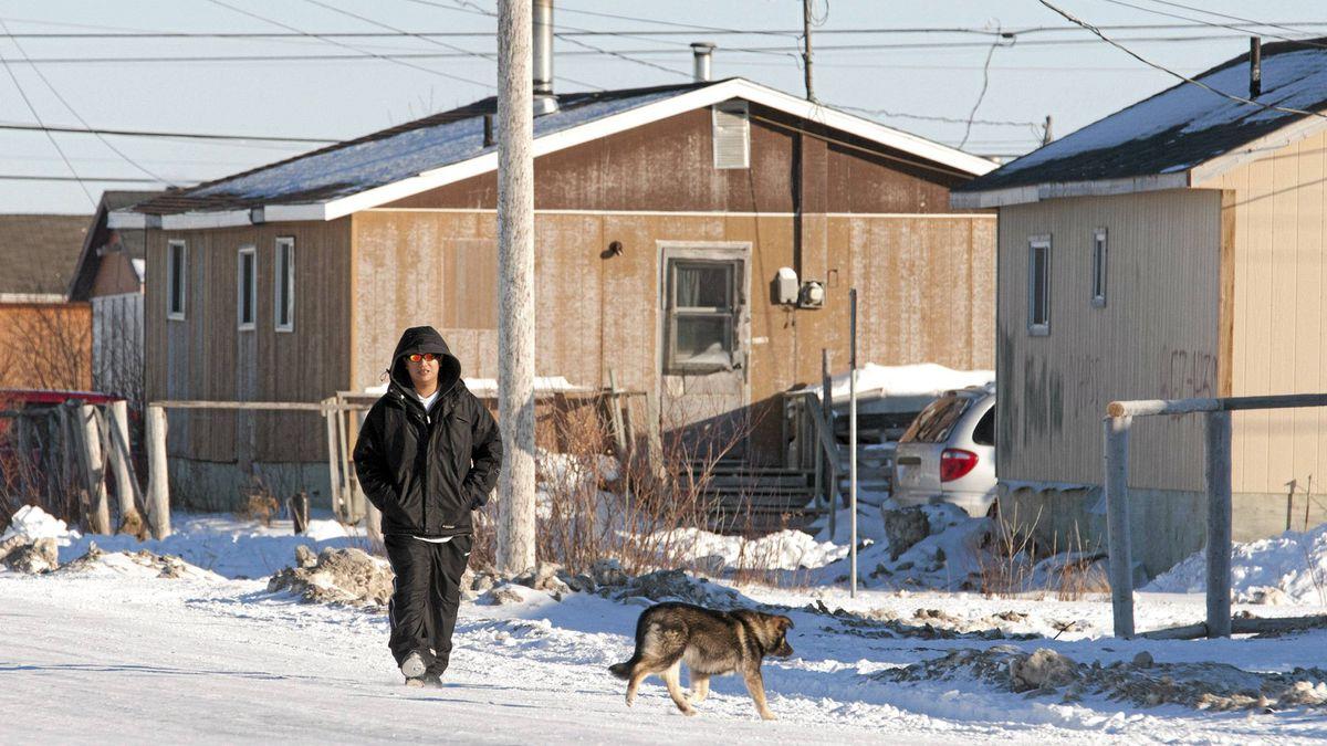A man walks down the street in Attawapiskat, Ont., Tuesday Nov. 29, 2011.