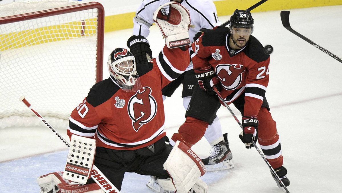 New Jersey Devils goalie Martin Brodeur (L) makes a save against the Los Angeles Kings as teammate Bryce Salvador follows the play and Kings' Anze Kopitar looks on in the second period of Game 1 of the Stanley Cup final in Newark, New Jersey, May 30, 2012.