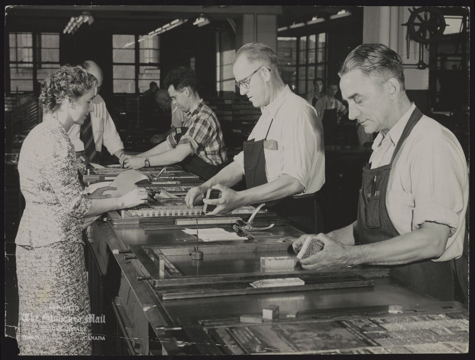 TORONTO GLOBE AND MAIL - HISTORICAL - PRODUCTION [The Globe and Mail - History - Production -- William H. Wright Building - Composing Room?. Credit: The Globe and Mail. Historical note: Production process: Makeup men place the galleys of type into page forms. When zinc cuts from the engraving room have been added, the forms are locked and sent to the stereotyping department where paperboard mats or impressions of the pages are made in a machine that operates at a pressure of 15,000 pounds a square-inch. Molten lead is poured over the paperboard mats and in 15 seconds lead plates are ready to be trimmed and dispatched to the presses. Taken from Dec. 14, 1957 edition.]