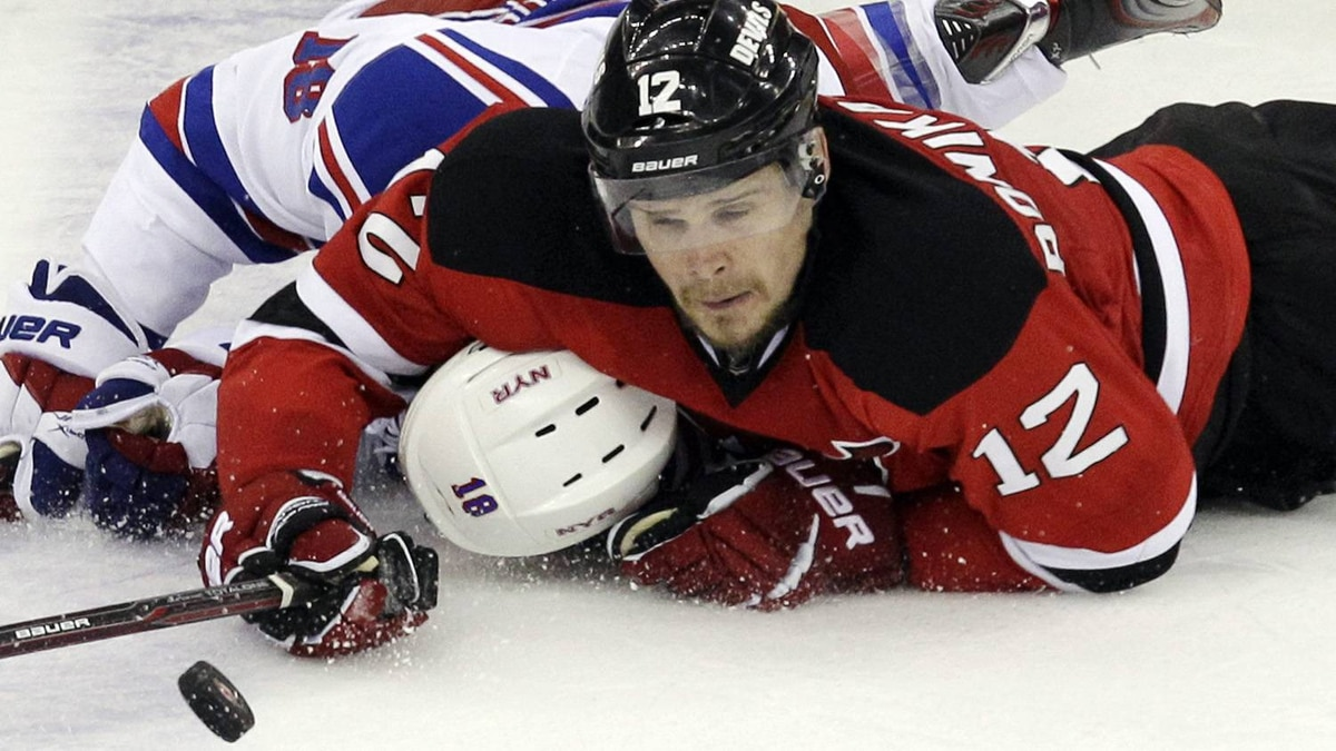 New Jersey Devils' Alexei Ponikarovsky, of Ukraine, right, and New York Rangers' Marc Staal struggle to reach the puck during the second period of Game 4 of an NHL hockey Stanley Cup Eastern Conference final playoff series, Monday, May 21, 2012, in Newark, N.J. (AP Photo/Kathy Willens)