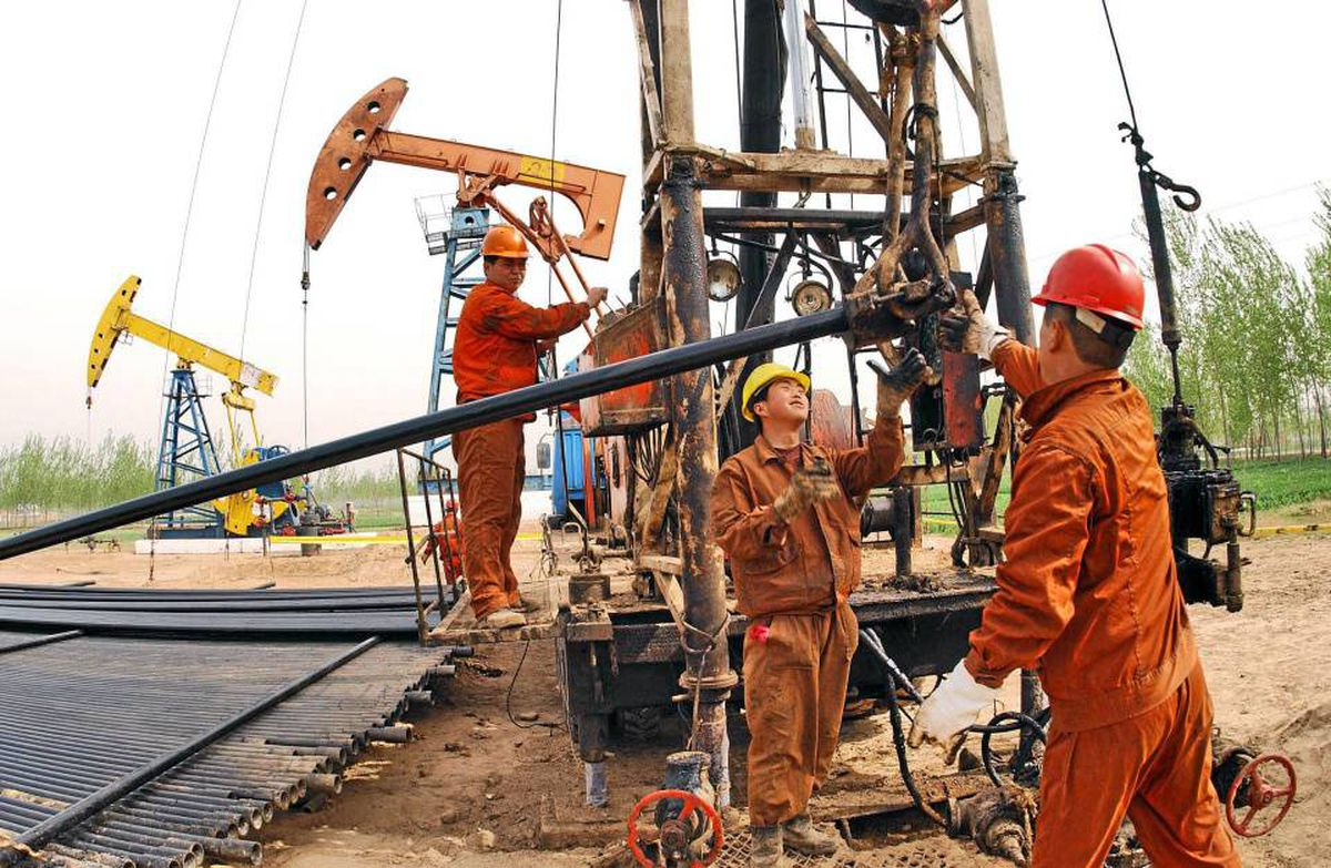 Workers from China's Sinopec Corp. work on an oil field in Puyang county of Henan province, central China.