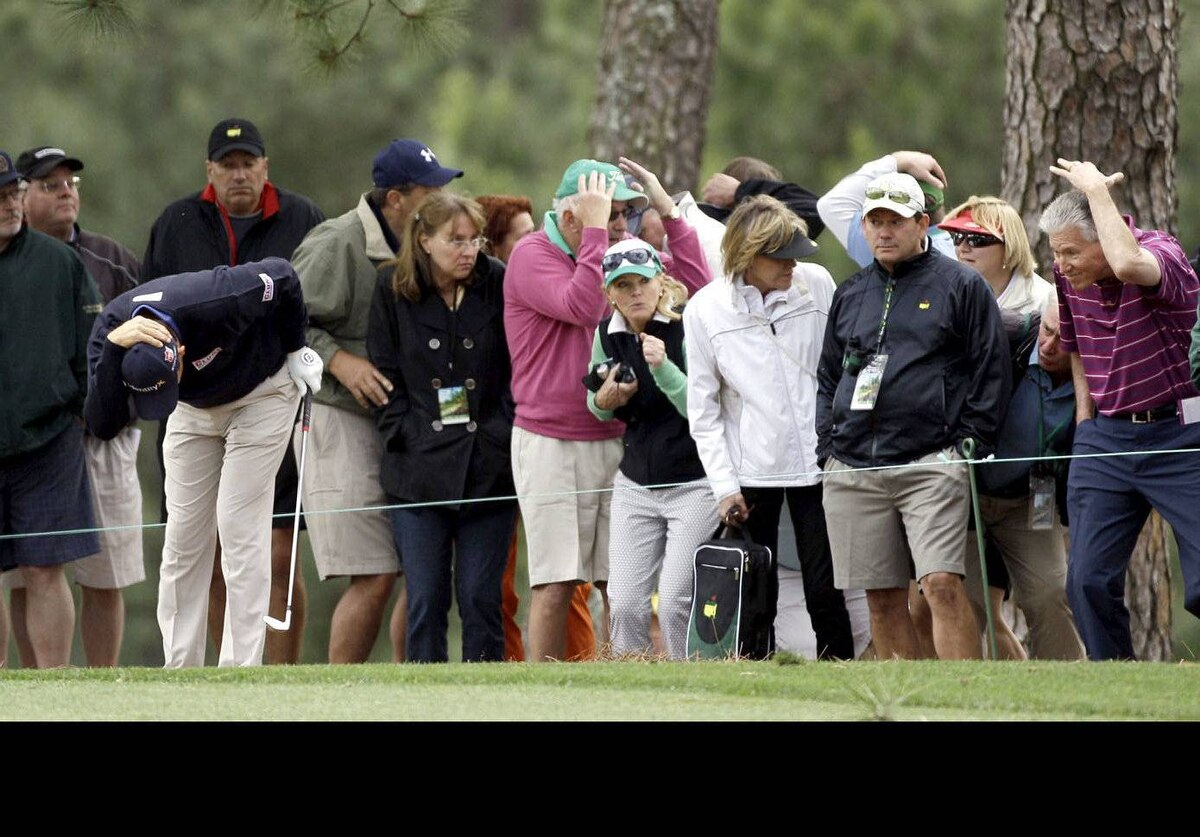 Padraig Harrington, of Ireland, and surrounding gallery on the first fairway duck after an unknown player yelled fore from another fairway during the second round the Masters golf tournament in Augusta, Ga.