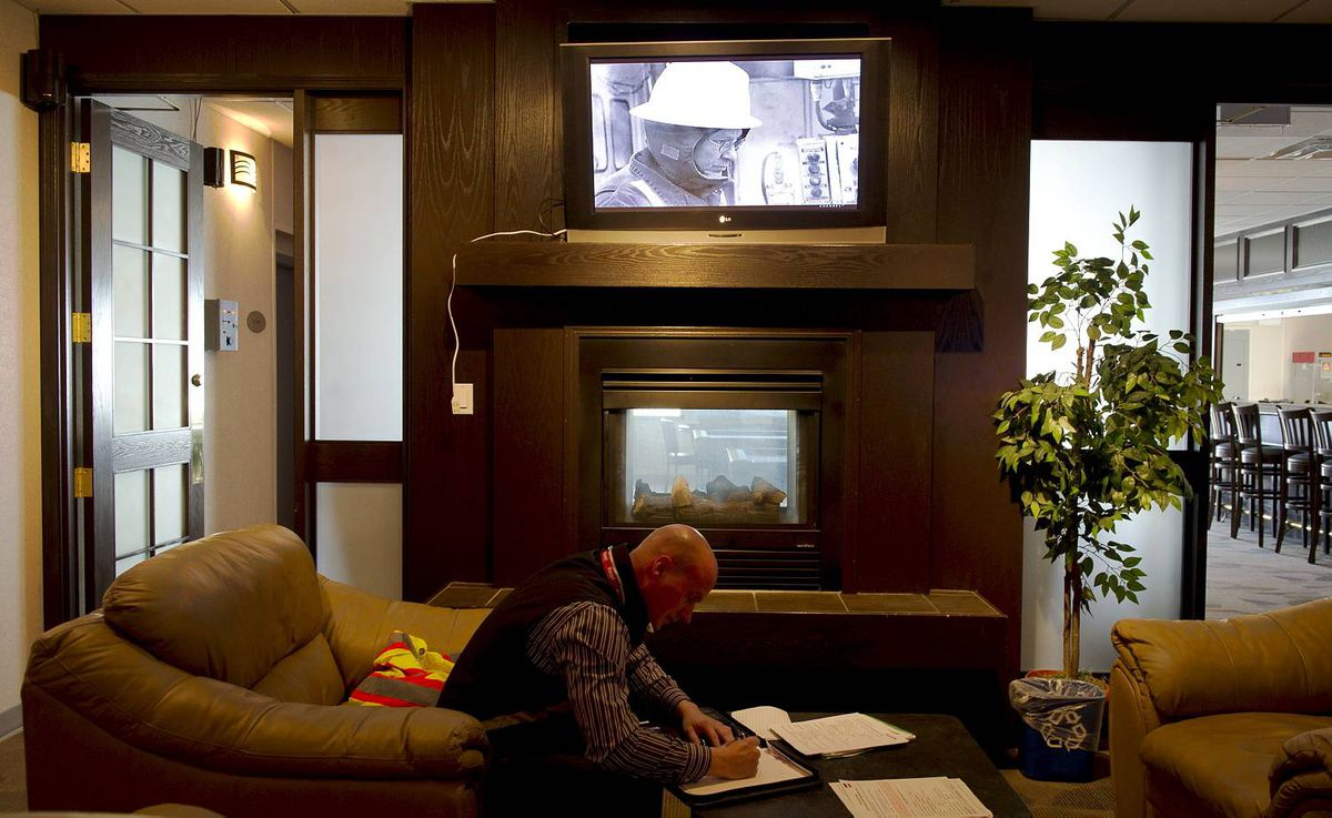 A worker reviews some paper work in one of the lounge areas complete with leather furniture, fire places and flat screen telelvisions at the Wapasu Lodge located north of Fort McMurray, Ab. Sept. 1/2010. Oil sands companies are adding a variety of luxury amenities at their work camps in order to attract and maintain staff. (Photo by Kevin Van Paassen/The Globe and Mail)