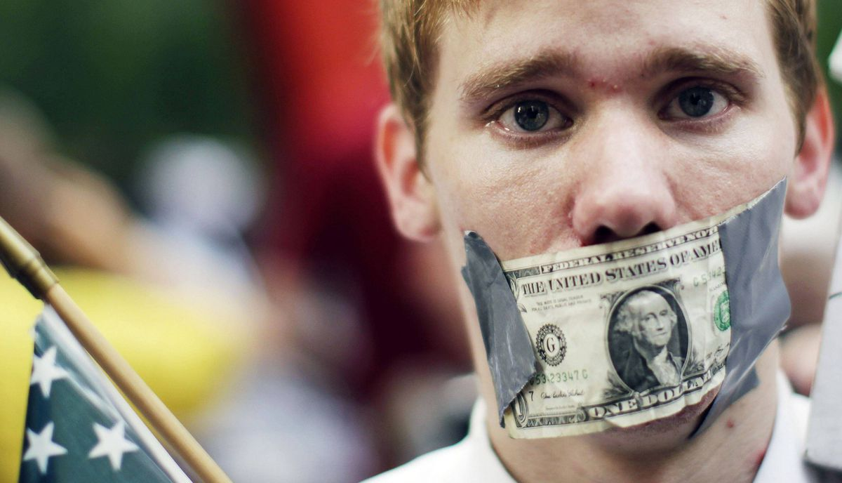 A demonstrator from the Occupy Wall Street campaign stands with a dollar taped over his mouth as he stands in Zucotti Park near the financial district of New York September 30, 2011.