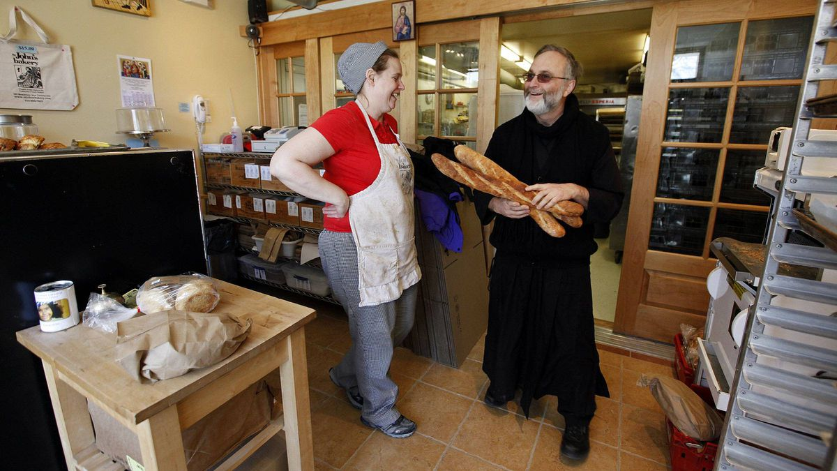 Stephanie Smith laughs with Father Roberto Ubertino, executive director of St. John the Compassionate Mission and St. John's Bakery