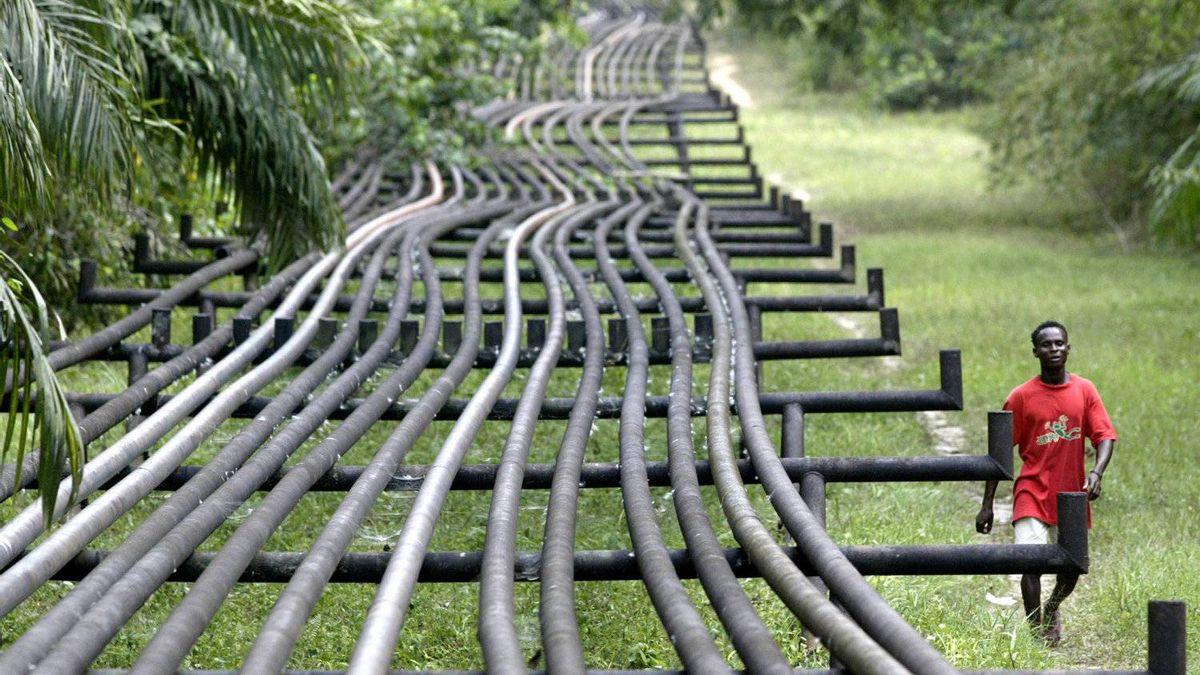 An unidentified man walks along oil pipelines belonging to Italian oil company Agip in Obrikom, Nigeria