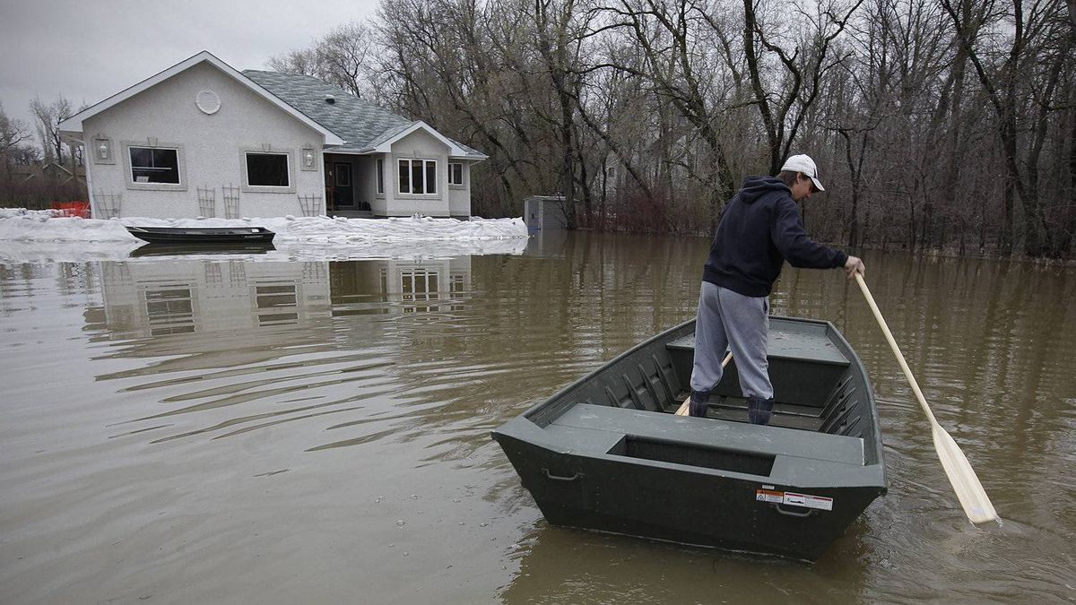 Bryan Ezako, owner of a home which is surrounded by water on Golden Oak Cove, boats to his home near St. Francis Xavier, Man., Tuesday, May 9, 2011. Flood waters from the Assiniboine River are threatening several communities.