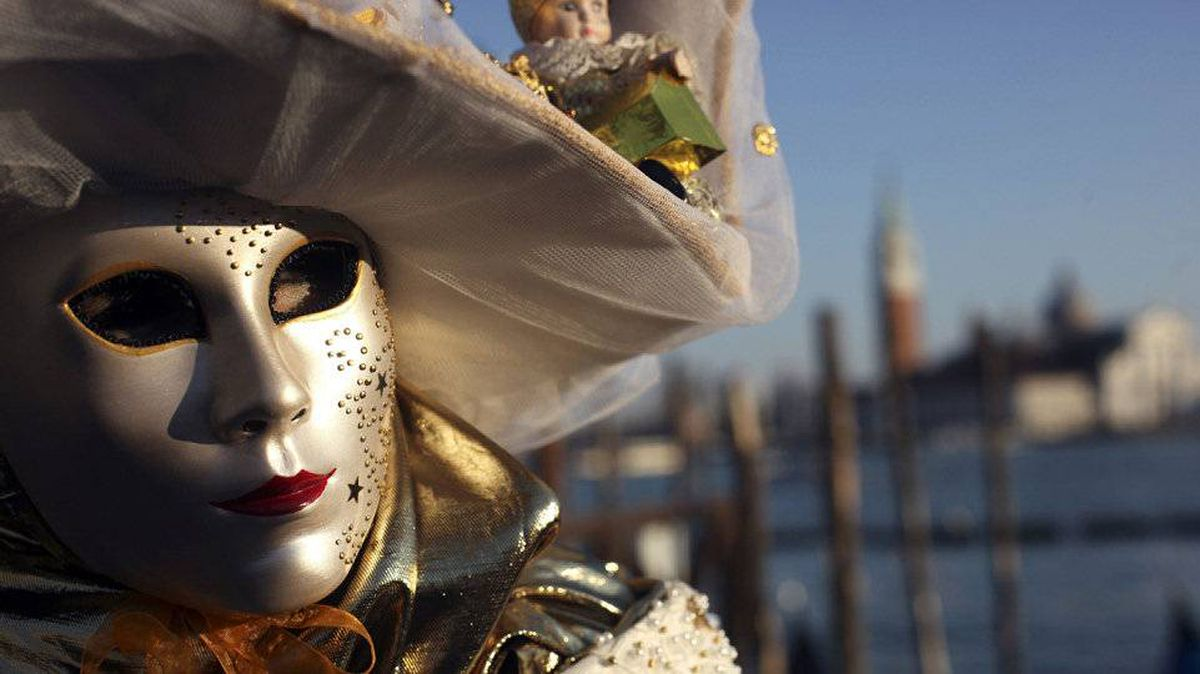 A masked reveller poses in Saint Mark's Square during the Venetian Carnival, February 21, 2012.