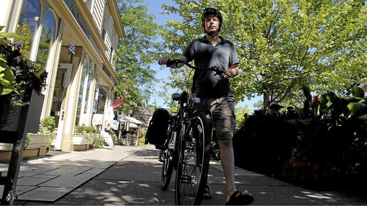 Globe and Mail Theatre critic Kelly Nestruck walks his bike down Queen Street in Niagara On The Lake. Photo By Sheryl Nadler