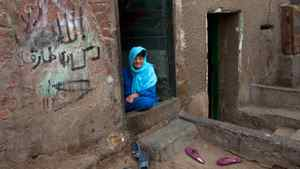 A woman sits on the ground at the entrance of her home in the Sayeda Zeinab neighbourhood of Cairo, Egypt on November 24, 2011.