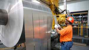 An employee at Alcoa Warrick Operations inspects finished rolls of aluminum.