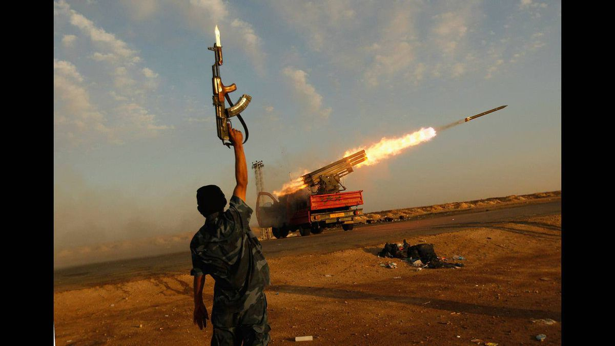 A rebel fighter celebrates as his comrades fire a rocket barrage toward the positions of troops loyal to Libyan ruler Muammar Gaddafi April 14, 2011 west of Ajdabiyah, Libya.
