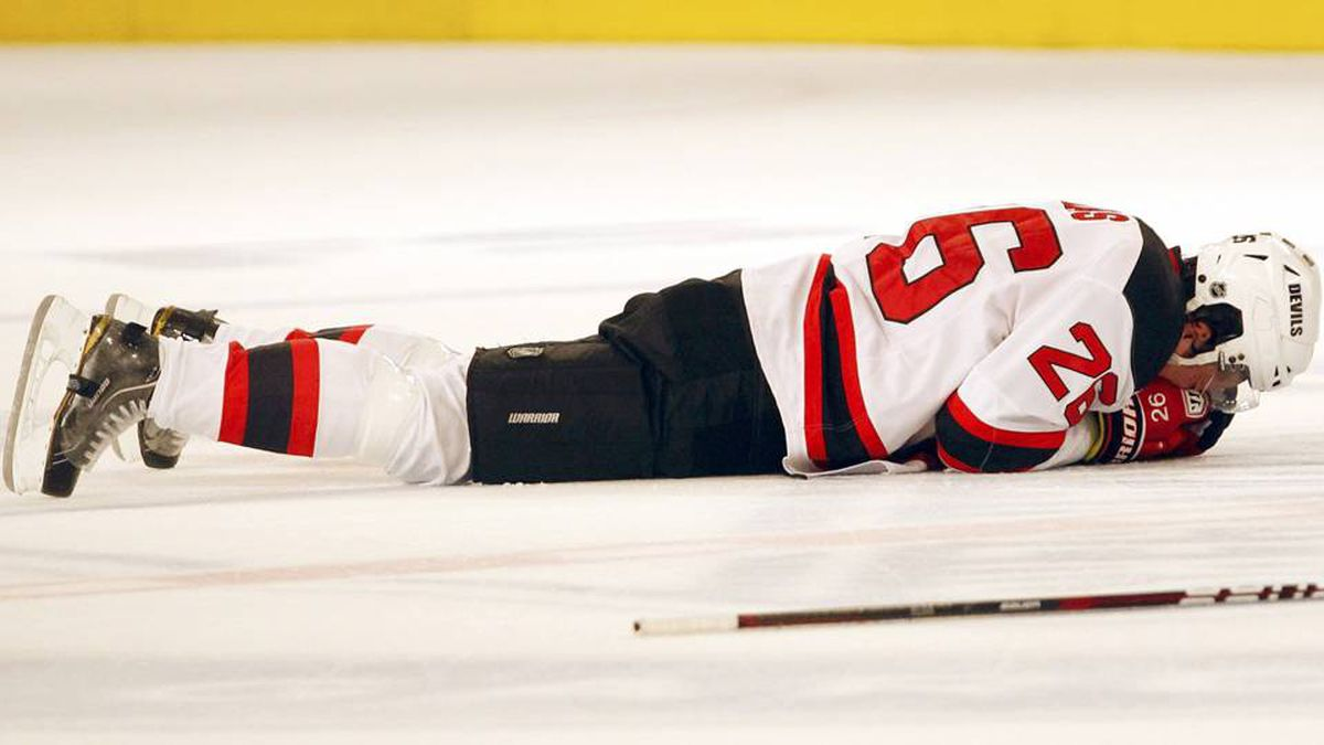 New Jersey Devils' Patrik Elias lies on the ice and holds his hand to his face after suffering an injury in the first period against the New York Rangers during Game 1 of the NHL Eastern Conference Finals