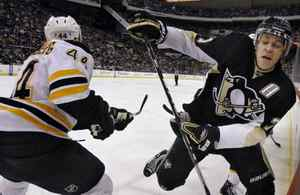 Boston Bruins' Dennis Seidenberg, left, checks Pittsburgh Penguins' Evgeni Malkin, of Russia, into the boards in the second period of an NHL hockey game in Pittsburgh, Sunday, March 7, 2010. (AP Photo/Keith Srakocic)