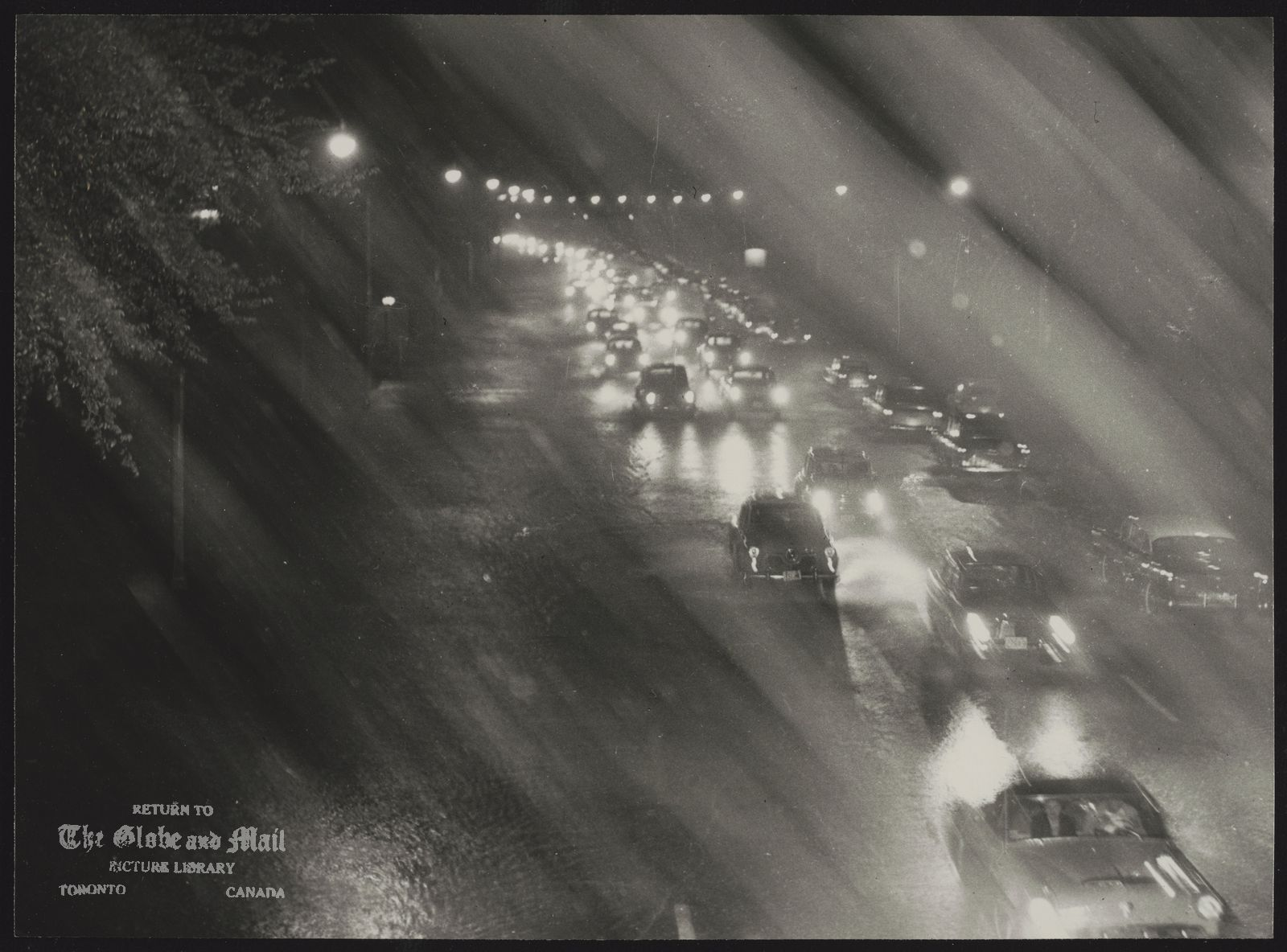 The notes transcribed from the back of this photograph are as follows: Homeward bound motorists on Lake Shore Rd. south of CNE during height of downpour, Oct. 15, 1954. [HURRICANE HAZEL HITS TORONTO -- Homeward bound motorists are packed in solid, sodden lines on Lake Shore Road, south of the CNE grounds, during height of the downpour on October 15, 1954. Steady rain and strong winds tied up traffic in nearly every section of the city. This photo was taken from a Bailey Bridge spanning the highway. Hurricane Hazel pounded the city of Toronto with 110 km/hr winds and more than 200 millimetres of rain in less than 24 hours. Thousands were left homeless, and 81 were killed as severe flooding devastated low-lying areas in and around the city. Areas to the west were especially hard hit and property damage was extensive as bridges and streets were washed out and homes washed away. Photo by Richard Cole / For The Globe and Mail (Neg. #54288-2)]