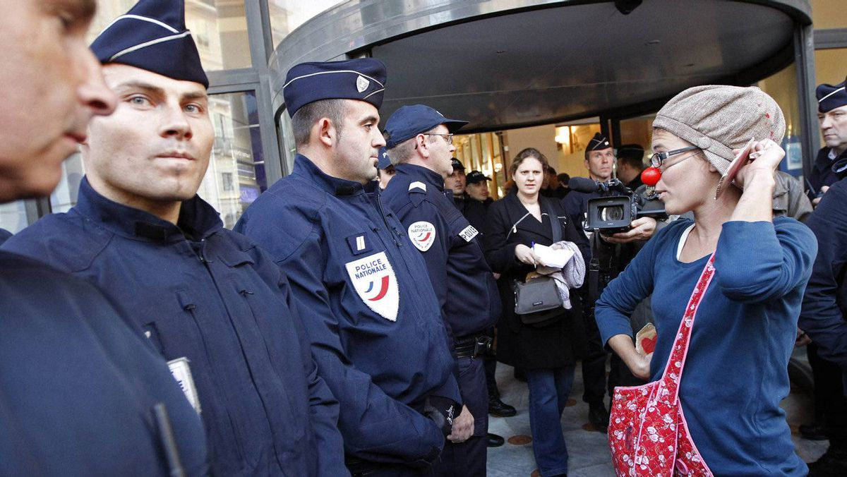 An anti-G20 demonstrator faces French police as she exits a bank after a demonstration in Nice, Nov. 2, 2011. G20 leaders will gather in nearby Cannes for the final summit of France's presidency Nov. 3-4. REUTERS/Jean-Paul Pelissier