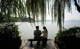 CHINA. Hangzhou. A young couple sit next to the famous West Lake. 2009