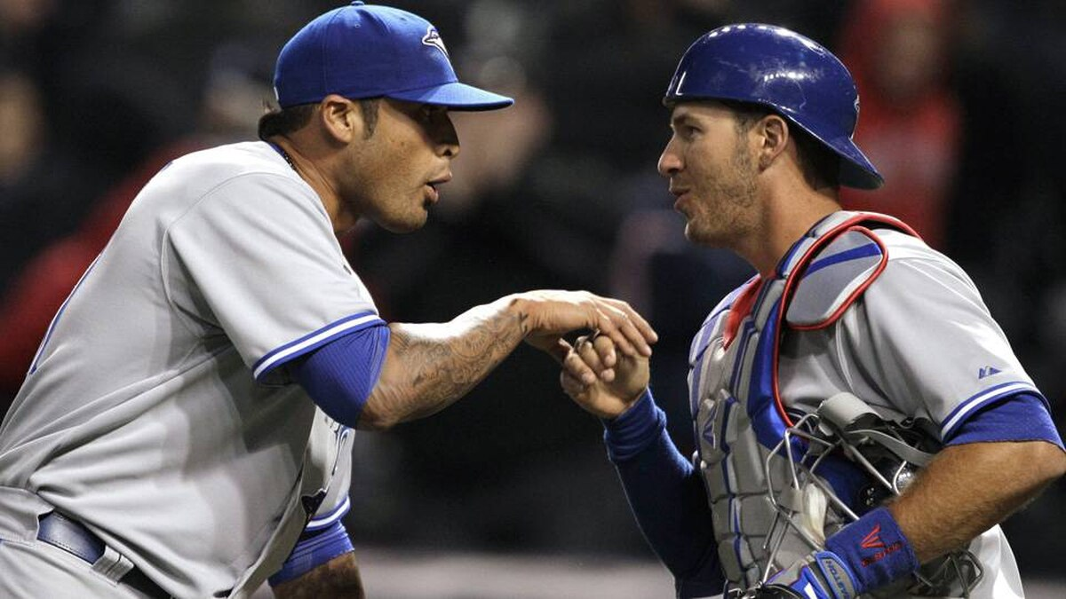 Toronto Blue Jays relief pitcher Sergio Santos, left, congratulates catcher J.P. Arencibia after the Blue Jays defeated the Cleveland Indians 7-4 in 16 innings.