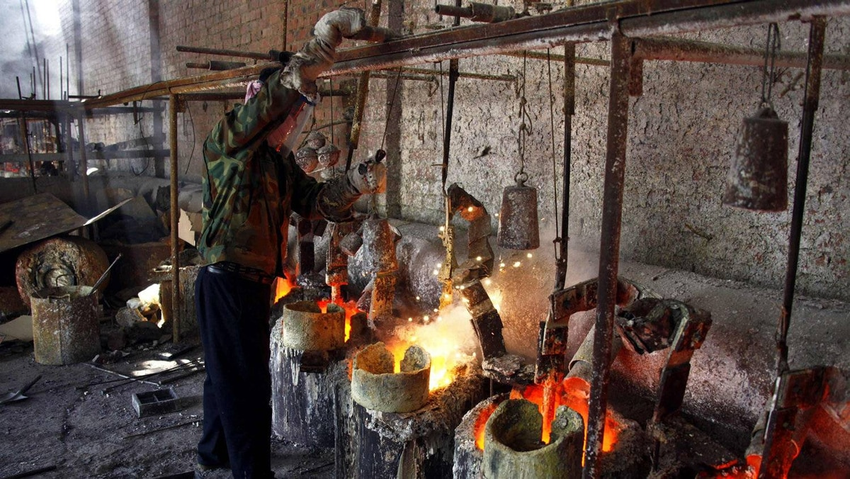 A worker at Jinyuan Co.'s smelting workshop stokes the pots containing the rare earth metal Lanthanum before he pours it into a mould.