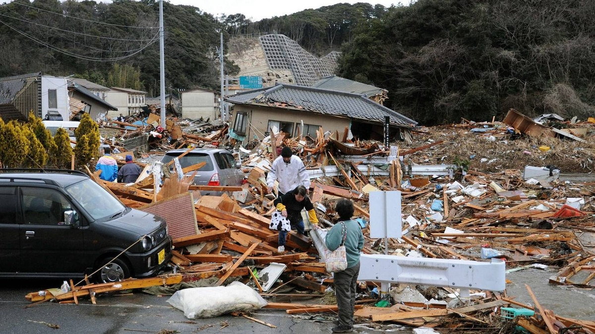 Residents walk through the wreckage in Iwaki, Fukushima prefecture.